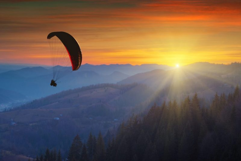 Paraglider silhouette flying in a light of colorful sunrise in a Carpathian mountain valley. Majestic landscape. Ukraine, Europe
